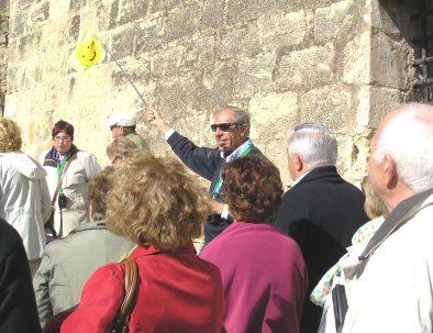 Guía oficial de turismo liderando a un grupo de excursionistas y explicando los detalles del tour